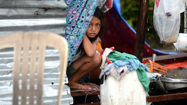 Một bé gái ngồi trong căn lều tạm, sỡ hãi nhìn ra ngoài đường.