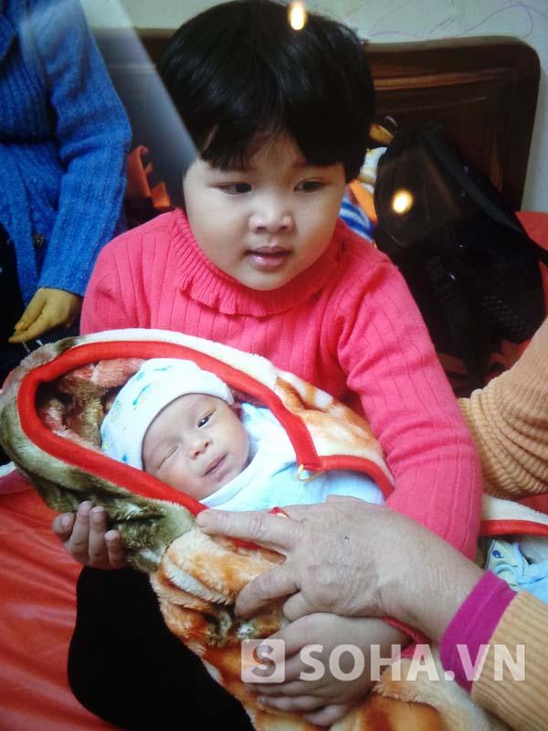 Bé Hải Bình cũng rất hạnh phúc khi bế em trai trên tay