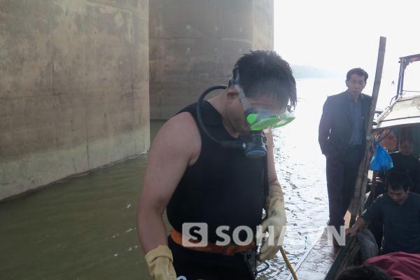 Một trong 2 thợ lặn đầu tiên chuẩn bị nhảy xuống sông.