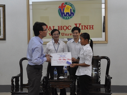 Anh Tào Đức Hiệp cũng lãnh đạo Trường ĐH Vinh trao số tiền hỗ trợ 4 năm ăn học cho em Vi Thị Tâm