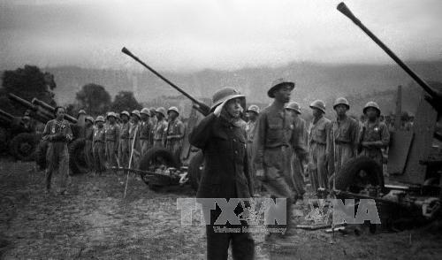 """Đại tướng Võ Nguyên Giáp duyệt các đơn vị tham gia chiến dịch Điện Biên Phủ tại Lễ mừng chiến thắng ngay tại mặt trận, trao cờ """"Quyết chiến quyết thắng"""" của Chủ tịch Hồ Chí Minh cho các đơn vị lập công và tuyên dương các tập thể, cá nhân có nhiều thành tích trong chiến đấu. Ảnh: Tư liệu TTXVN"""