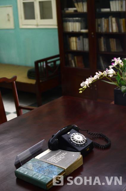 Trên bàn có đặt một chiếc điện thoại và 2 cuốn sách