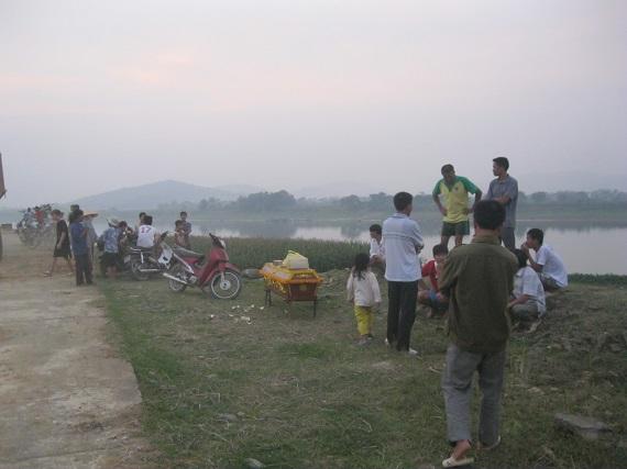 Nhiều người hiếu kì tập trung bên bờ sông.