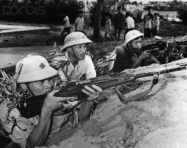7/16/1965-Hanoi, North Vietnam: Children play nearby as members of a North Vietnamese self-defense team train. Many such teams and militia units have been formed in North Vietnam. --- Image by © Bettmann/CORBIS