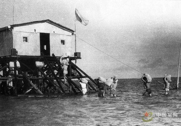 Sĩ quan và binh lính Trung Quốc vận chuyển vật tư xây dựng bằng tay để xây dựng những căn nhà trái phép.