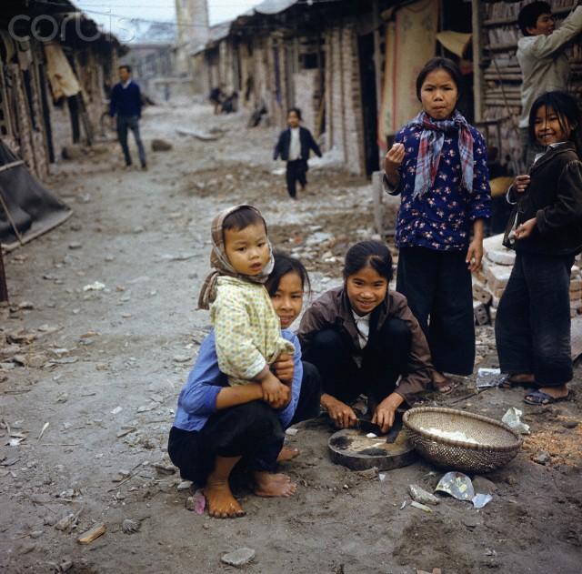 Các bé gái đang chuẩn bị cơm trưa bên những gian nhà tạm ở phố Khâm Thiên sau khi dãy phố này bị không quân Mỹ san phẳng cuối năm 1972. Ảnh: Nhiếp ảnh gia Werner Schulze.