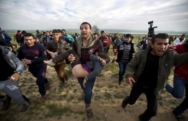 Người dân Palestine bế một bé trai bị thương trong cuộc đụng độ với lực lượng an ninh Israel gần biên giới  ở Dải Gaza.