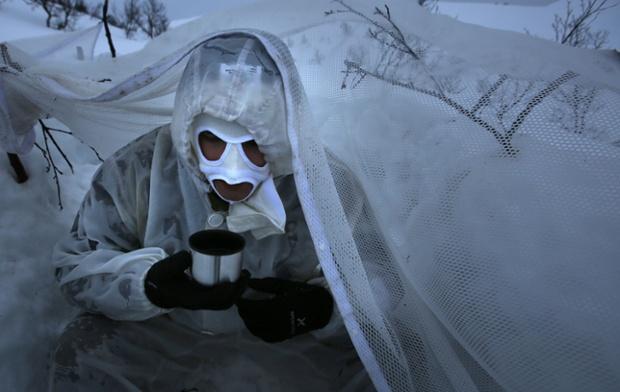 Một lính thủy đánh bộ Hoàng gia Anh sưởi ấm trong giờ nghỉ của khóa huấn luyện kỹ năng dười trời lạnh giá ở Harstad, Na Uy.