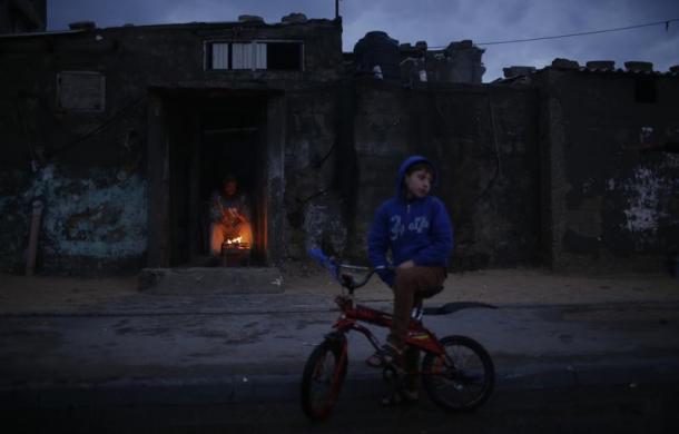 Một người đàn ông Palestine sưởi ấm cạnh bếp lửa trong nhà tại trại tị nạn Shati ở Dải Gaza.