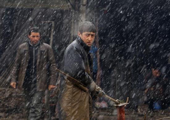 Những người lao động làm việc dưới mưa trên đường phố ở Kabul, Afghanistan.
