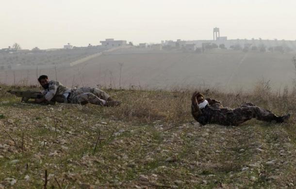 Chiến binh phiến quân Syria bò trên mặt đất trong khi chiến đấu với quân đội chính phủ ở thị trấn Souran.