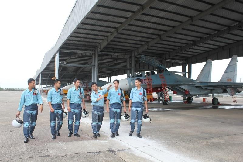 Đại úy phi công Đặng Đức Công (thứ ba từ phải sang), biên đội trưởng đang chia sẻ kinh nghiệm bay với các phi công trẻ sau chuyến bay làm nhiệm vụ