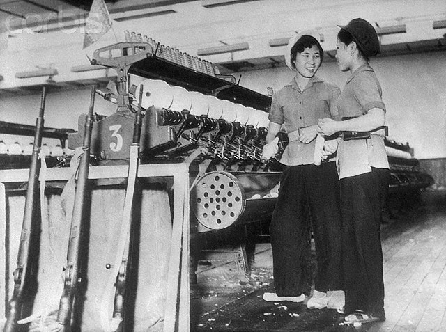 8/14/65-Hanoi, Vietnam: With the stepped up air attacks against targets in North Viet Nam, defense measures have been increased throughout that country. Here, women factory workers in the capital of Hanoi keeep their rifles next to their machine as they go about their jobs. --- Image by © Bettmann/CORBIS
