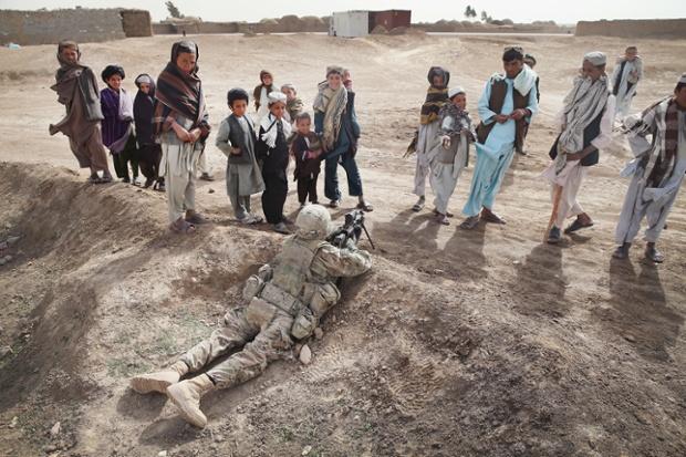 Trẻ em đứng nhìn một binh sĩ Mỹ đang giữ chốt trong khi tuần tra tại một ngôi làng gần Kandahar, Afghanistan.