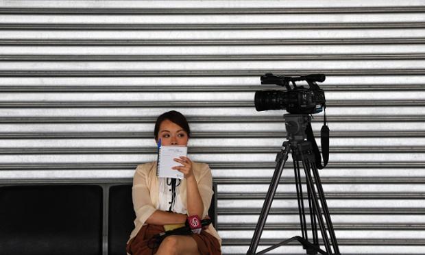 Một nữ phóng viên từ Trung Quốc chợ cạnh camera tại sân bay quốc tế Kuala Lumpur khi các cuộc tìm kiếm máy bay MH370 mất tích của hãng hàng không Malaysia Airlines vẫn tiếp tục.