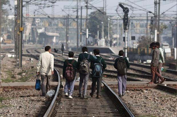 Học sinh đi trên đường ray trên đường tới trường ở New Delhi, Ấn Độ.