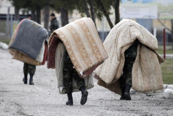 Các binh sĩ Ukraine mang theo chăn đệm tại một căn cứ quân sự bên ngoài ngôi làng Perevalnoye ở Simferopol.