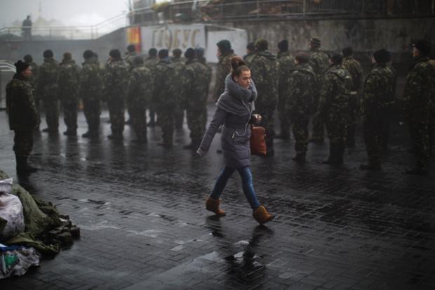 Một phụ nữ đi qua các tân binh Ukraine trên quảng trưởng Độc lập ở thủ đô Kiev.