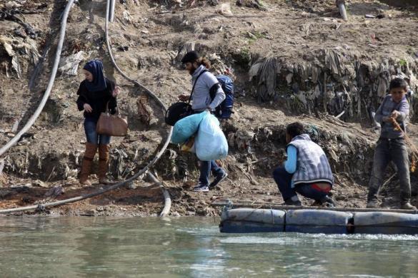Người dân cố gắng vượt biên trái phép từ Syria sang Thổ Nhĩ Kỳ qua con sông Assi.
