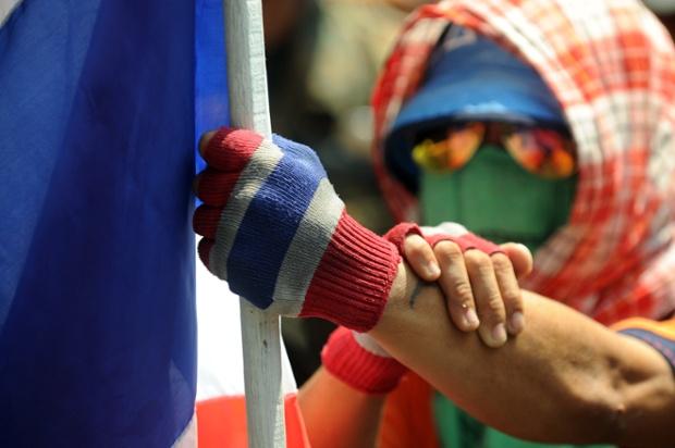 Người biểu tình cầm cờ với cử chỉ thách thức đứng bên ngoài trụ sở cảnh sát ở Bangkok.