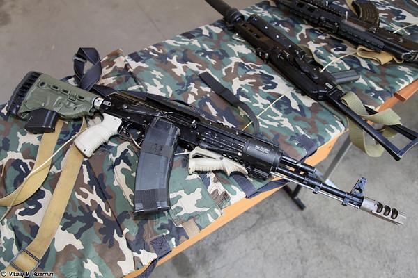 Súng trường tiến côn AK-74M,  khẩu súng trên đã được nâng cấp với loa che lửa kiểu mới cùng các bộ ray Picantinny và báng súng rút.