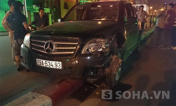 Phần đầu chiếc xe ô tô bị nát bét phía bên trái, két nước bị vỡ làm tung tóe nước ra đường, lốp trước phía bên trái của chiếc xe ô tô cũng bị nổ.