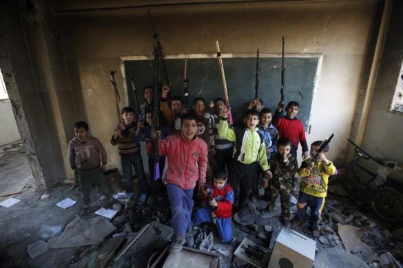 Trẻ em chụp ảnh với súng đồ chơi trong một trường học bị tàn phá ở Syria.