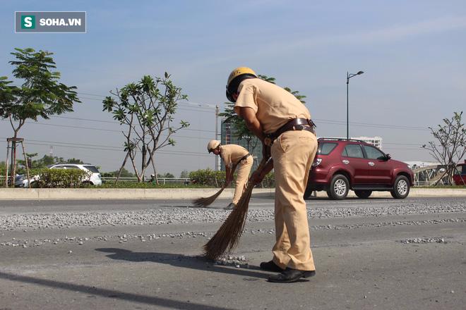Cảnh sát giao thông đội nắng quét đá rơi vãi trên đường ở Sài Gòn - Ảnh 1.