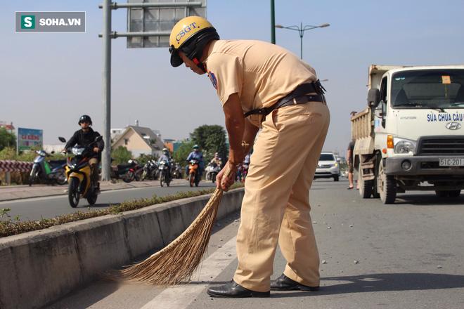 Cảnh sát giao thông đội nắng quét đá rơi vãi trên đường ở Sài Gòn - Ảnh 2.
