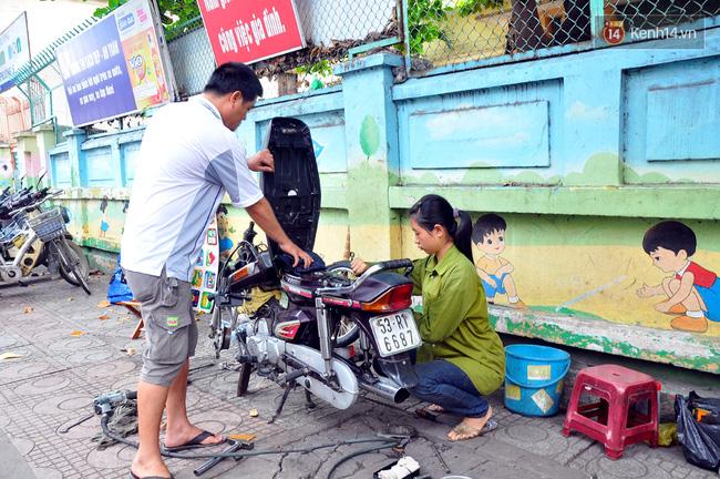 Cô gái 21 tuổi sửa xe máy ở vỉa hè Sài Gòn để phụ ba mẹ nuôi các em ăn học - Ảnh 1.
