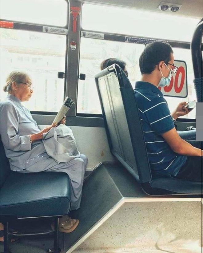 Khoảnh khắc đối lập trên chuyến bus: Một thanh thản bên tờ báo giấy, một chúi đầu vào smartphone - Ảnh 1.