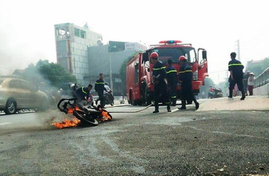 Người phụ nữ ôm cháu tháo chạy khỏi xe máy cháy ngùn ngụt giữa phố - Ảnh 1.