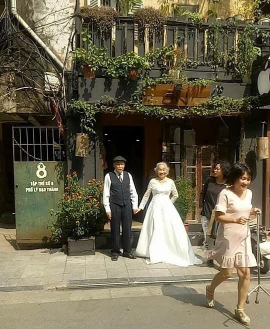 Hình ảnh cô dâu tóc bạc mặc váy cưới trắng, chú rể chống gậy móm mém cười trên phố Hà Nội gây sốt mạng - Ảnh 1.