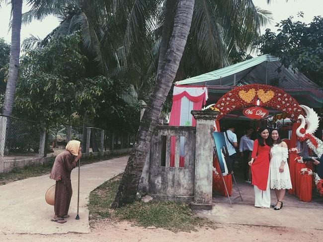 2 cô gái xinh đẹp chụp ảnh ở cổng rạp cưới nhưng hình ảnh cụ bà chống gậy đứng bên đường lại khiến nhiều người chú ý - Ảnh 1.