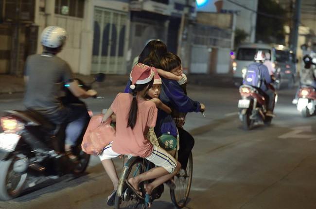 Khoảnh khắc lay động: Giáng sinh về sớm trên mái đầu trẻ thơ, mẹ chở 3 con trên chiếc xe đạp cũ - Ảnh 1.