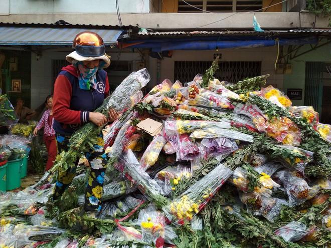 Hoa Tết đổ bỏ chất đống thành 'núi' tại chợ hoa lớn nhất Sài Gòn - Ảnh 1.