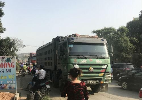 Nhóm thanh niên lạ mặt phân luồng cho xe tải chở đất, gây ách tắc đường mòn Hồ Chí Minh  - Ảnh 2.