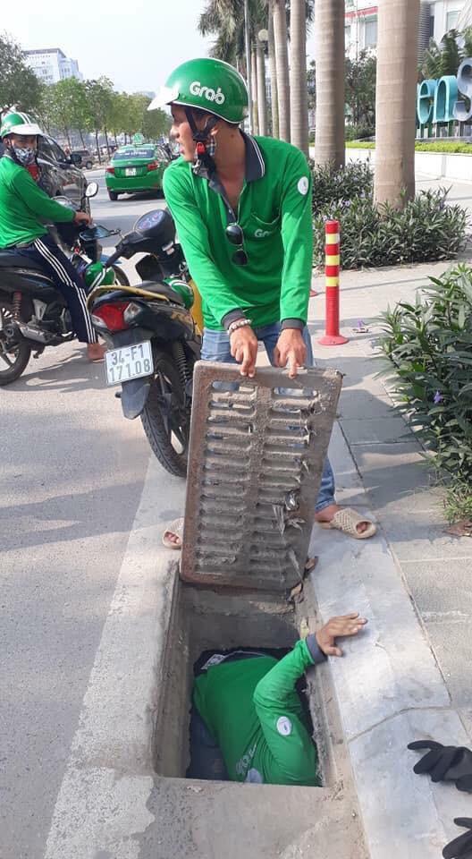 Hình ảnh đẹp: Hai tài xế GrabBike chui xuống cống để nhặt đồ hộ nữ du khách nước ngoài - Ảnh 1.