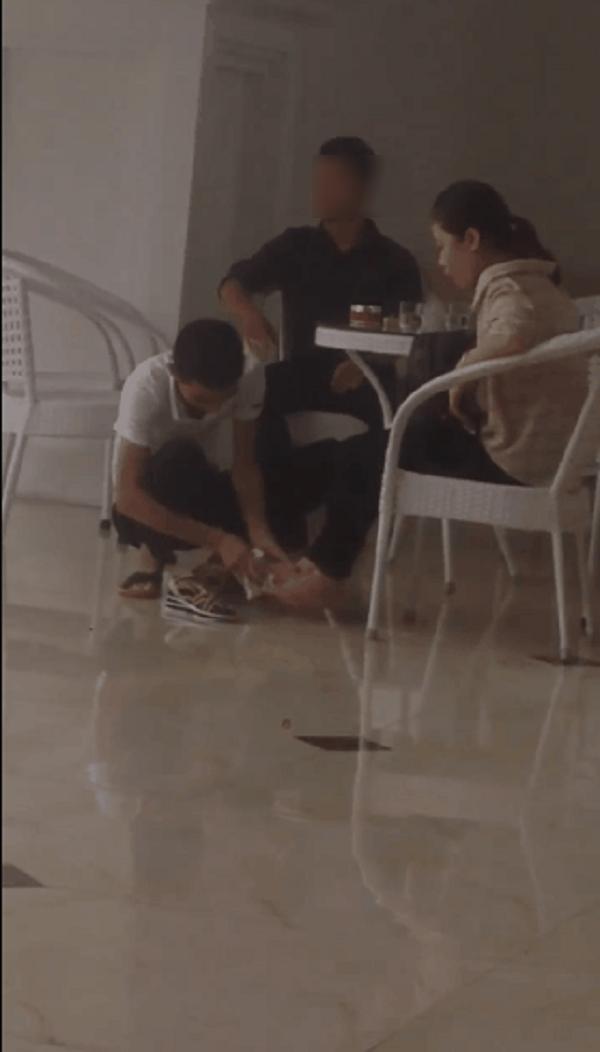 Sau cơn mưa, clip ghi lại cảnh chàng trai ngồi xổm lau dép, lau chân cho bạn gái gây tranh cãi - Ảnh 2.