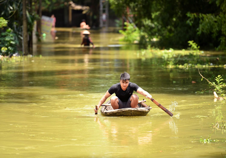 Sau 1 tuần mưa, người Hà Nội dùng thuyền tự chế, bơi trong dòng nước ngập ao bèo về nhà - Ảnh 4.