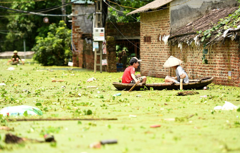 Sau 1 tuần mưa, người Hà Nội dùng thuyền tự chế, bơi trong dòng nước ngập ao bèo về nhà - Ảnh 28.