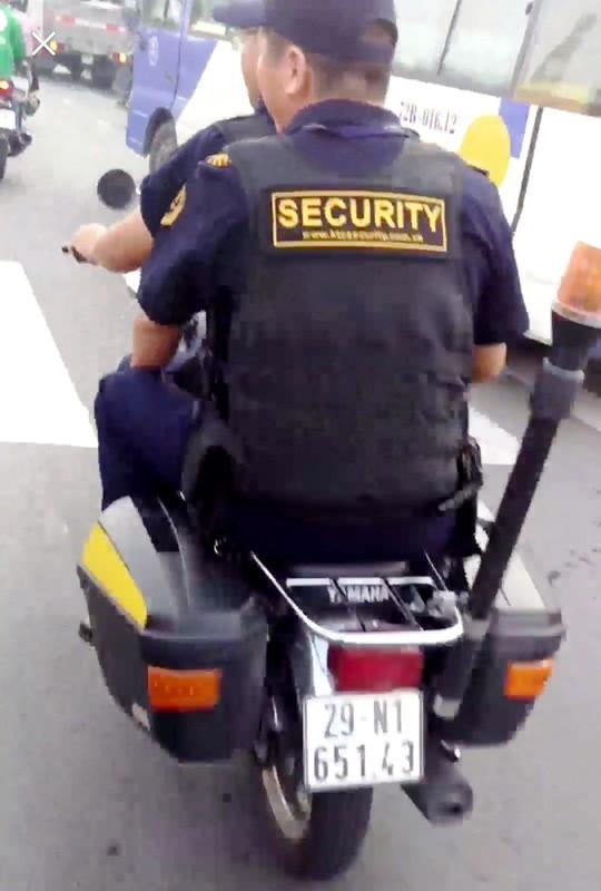 Bảo vệ giắt súng, không đội nón bảo hiểm… nghênh ngang trên đường - Ảnh 1.