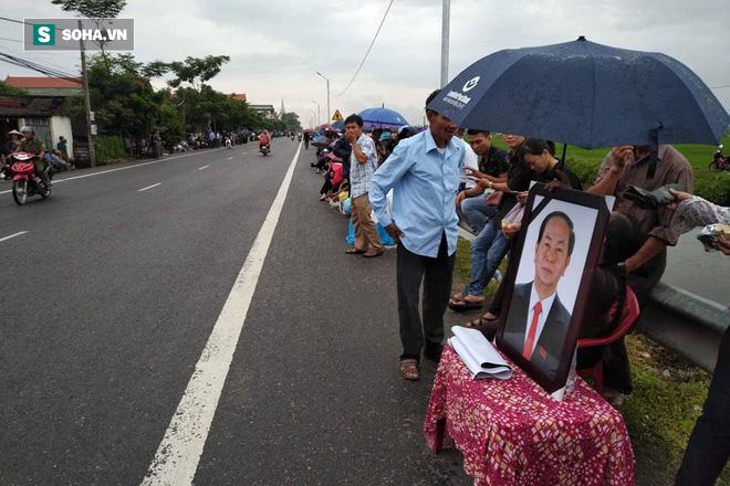 Người dân mang di ảnh Chủ tịch Trần Đại Quang đón đợi đoàn đưa linh cữu Chủ tịch.