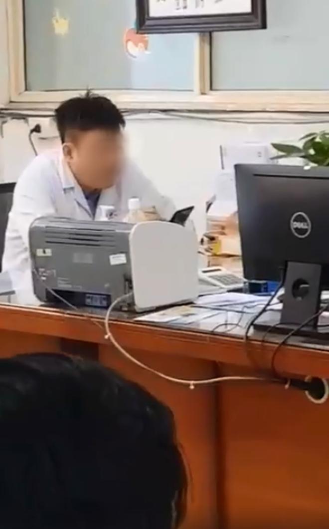 Xôn xao hình ảnh bác sĩ ngồi thản nhiên xem điện thoại dù bệnh nhân xếp hàng dài chờ đợi trong giờ hành chính - Ảnh 1.