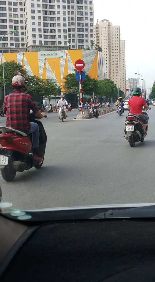 Người đàn ông ngoại quốc nằm vắt vẻo trên xe dựng giữa đường, hút thuốc gây tranh cãi - Ảnh 1.