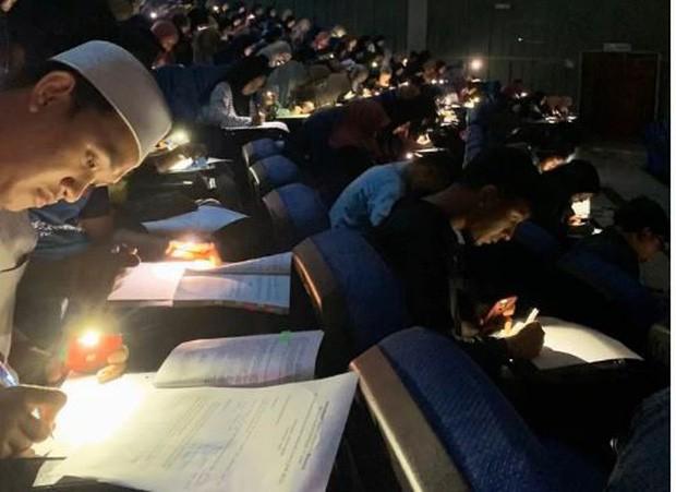 Chăm chỉ như sinh viên trường người ta: Cúp điện vẫn rọi đèn pin điện thoại để làm bài kiểm tra - Ảnh 1.