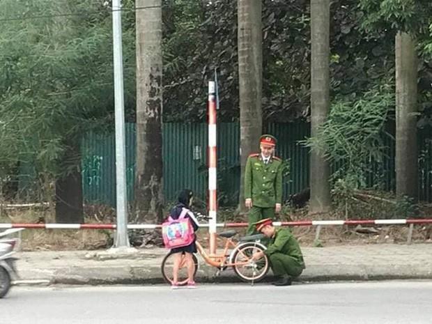 Hình ảnh 2 chú công an giúp bé gái đi học về sửa xe bị tuột xích được cộng đồng mạng chia sẻ mạnh - Ảnh 1.