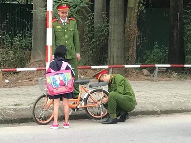 Hình ảnh 2 chú công an giúp bé gái đi học về sửa xe bị tuột xích được cộng đồng mạng chia sẻ mạnh - Ảnh 2.
