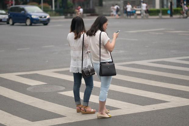 Trung Quốc phạt tiền người đi bộ xem điện thoại khi sang đường - Ảnh 1.