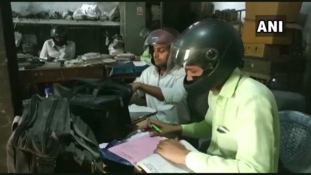 Đáng ngẫm hình ảnh công chức Ấn Độ đội mũ bảo hiểm trong phòng làm việc - Ảnh 1.